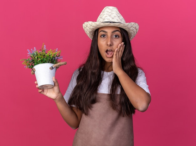 鉢植えの植物を保持しているエプロンと夏の帽子の若い庭師の女の子は、ピンクの壁の上に立って驚いて驚いた