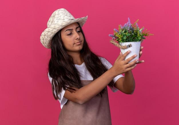 Молодая девушка-садовник в фартуке и летней шляпе держит горшок с растением и заинтригованно смотрит на него, стоя над розовой стеной