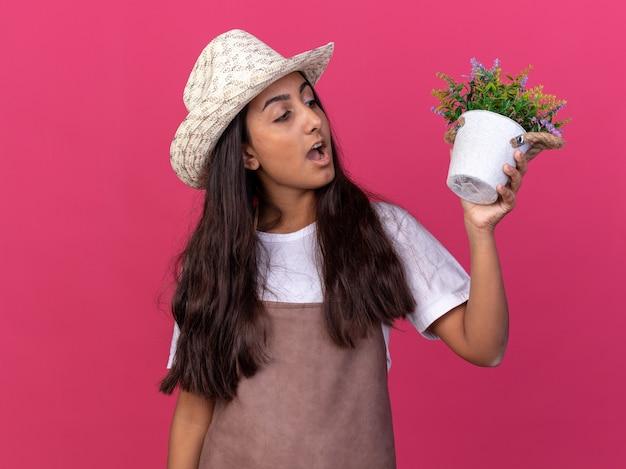 エプロンとそれを見て鉢植えの植物を保持している夏の帽子の若い庭師の女の子は、ピンクの壁の上に立って驚いて驚いた