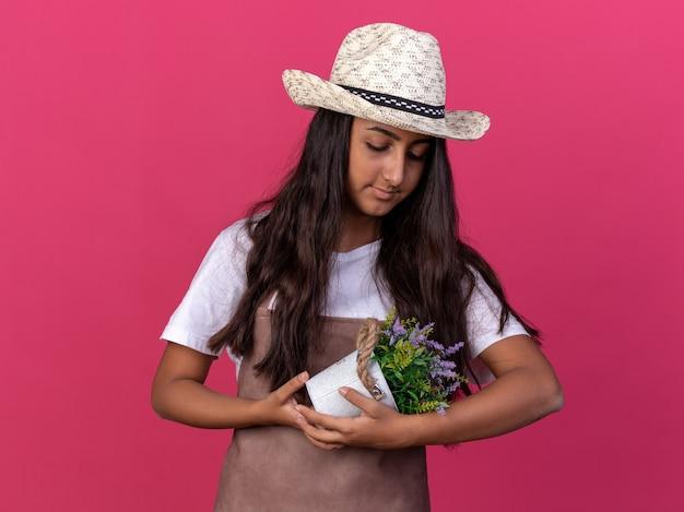 エプロンと夏の帽子をかぶった若い庭師の女の子は、ピンクの壁の上に立って笑顔で愛を込めてそれを見て鉢植えの植物を保持しています