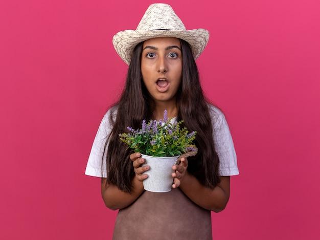 エプロンと鉢植えの植物を保持している夏の帽子の若い庭師の女の子は、ピンクの壁の上に立って驚いて驚いた
