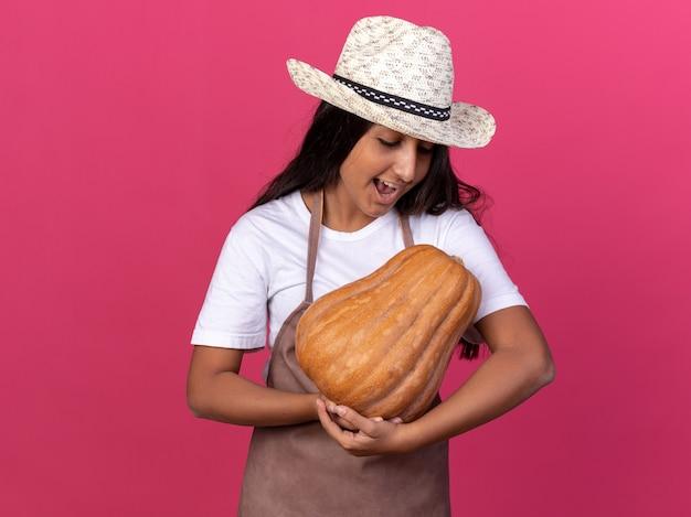 エプロンと夏の帽子をかぶった若い庭師の女の子がピンクの壁の上に立って幸せで陽気な顔に笑顔でそれを見てカボチャを保持しています