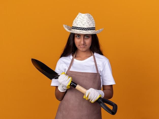 オレンジ色の壁の上に立っている自信を持って表情とシャベルを保持しているエプロンと夏の帽子の若い庭師の女の子