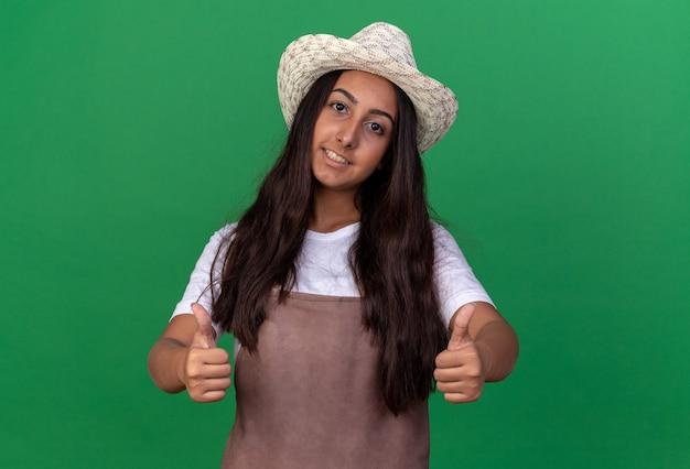 앞치마와 여름 모자에 젊은 정원사 소녀 녹색 벽 위에 서 엄지 손가락을 유쾌하게 보여주는 미소