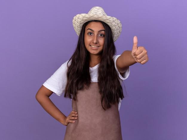 앞치마와 여름 모자에 젊은 정원사 소녀 보라색 벽 위에 서있는 엄지 손가락을 유쾌하게 보여주는 웃고