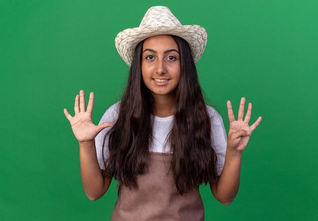 앞치마와 여름 모자에 젊은 정원사 소녀 녹색 벽 위에 서있는 번호 9를 보여주는 미소