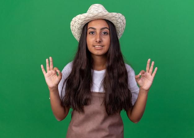 앞치마와 여름 모자에 젊은 정원사 소녀 녹색 벽 위에 서 양손으로 확인 표시를 보여주는 웃 고