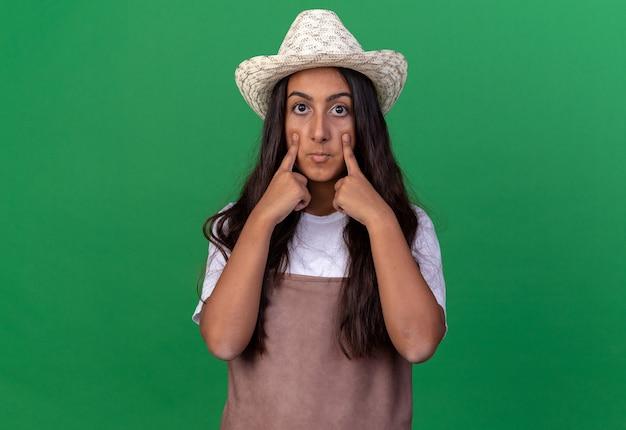 エプロンと夏の帽子の若い庭師の女の子は、緑の壁の上に立っている彼女の目に人差し指で指して驚いた
