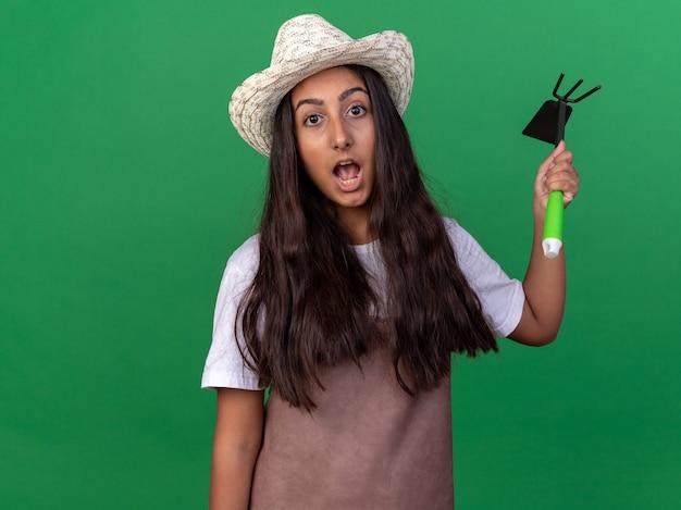 緑の壁の上に立って驚いてマットックを振るエプロンと夏の帽子の若い庭師の女の子