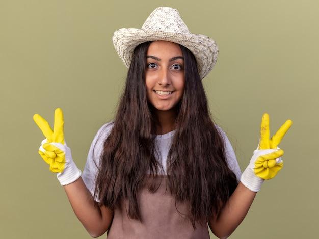 エプロンと夏の帽子をかぶった若い庭師の女の子は、緑の壁の上に立っているvサインを元気に笑顔で笑っています。