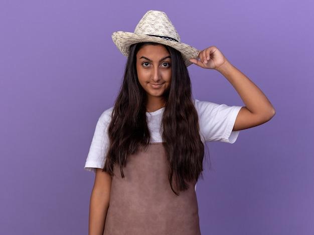 보라색 벽 위에 서있는 얼굴에 자신감이 미소로 앞치마와 여름 모자에 젊은 정원사 소녀
