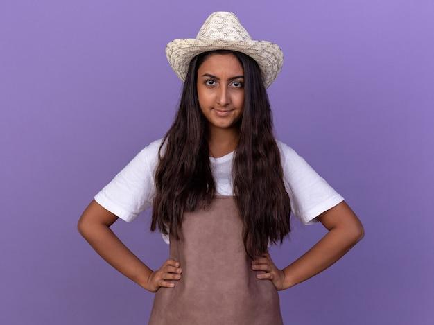 보라색 벽 위에 서있는 얼굴에 회의적인 미소로 앞치마와 여름 모자에 젊은 정원사 소녀