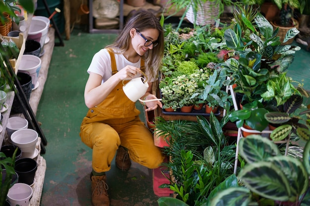 Молодая девушка-садовник работает в теплице с водой комнатных растений в горшках женский флорист уход за комнатными растениями