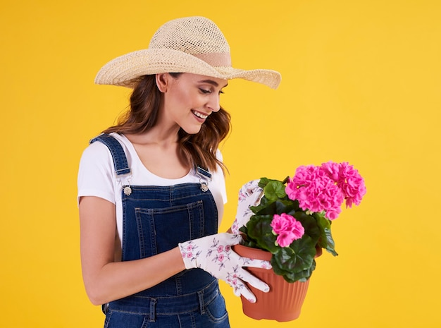美しいペラルゴニウムと植木鉢を保持している若い庭師