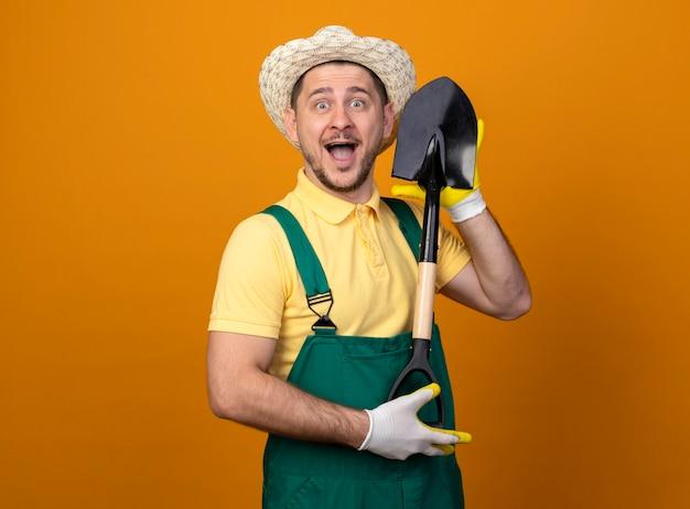 Молодой садовник в комбинезоне и шляпе демонстрирует лопату счастливой и веселой улыбкой, смотрящей вперед, стоящей над оранжевой стеной