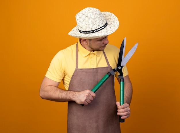 죄수 복과 모자를 쓰고있는 젊은 정원사는 오렌지 벽 위에 서서 그것을보고 울타리 가위를 들고