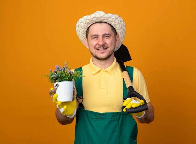 Молодой садовник в комбинезоне и шляпе держит лопату и горшечное растение, глядя вперед, улыбаясь со счастливым лицом, стоящим над оранжевой стеной