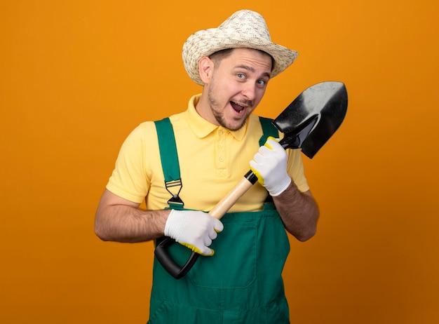オレンジ色の壁の上に元気に幸せで前向きに立って笑顔の正面を見てシャベルを保持しているジャンプスーツと帽子の若い庭師
