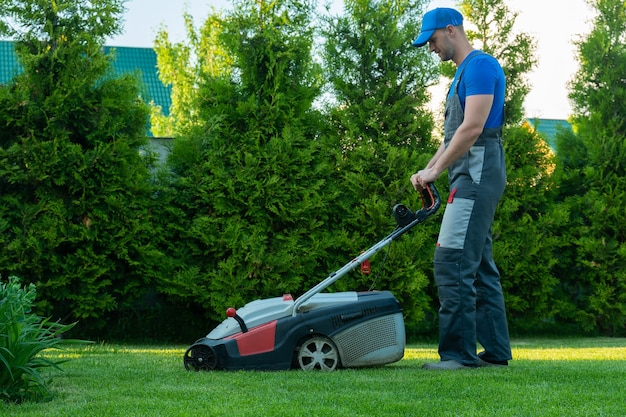 작업복을 입은 젊은 정원사는 줄거리에서 잔디 깎는 기계를 사용합니다