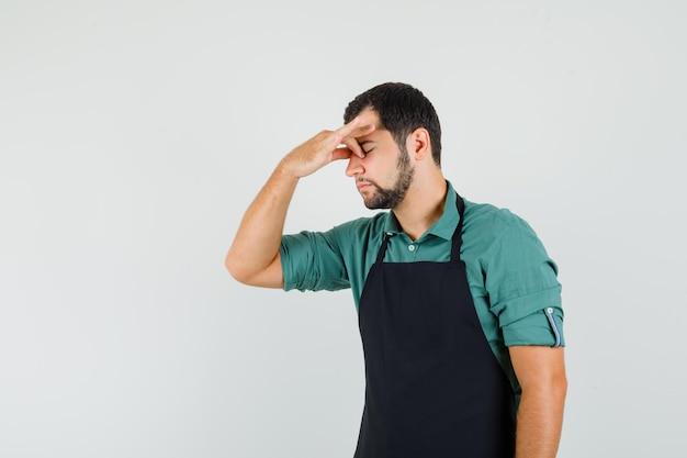 Tシャツを着た若い庭師、エプロンは彼の鼻に手を握り、疲れているように見えます。
