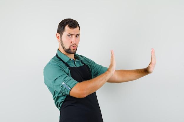 Tシャツを着た若い庭師、保護的な方法で手を保ち、注意深く見ているエプロン、正面図。
