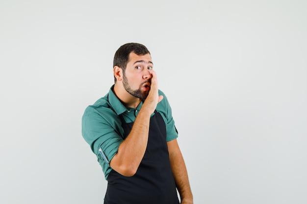 Молодой садовник в футболке, фартуке что-то говорит тайком и смотрит сосредоточенно, вид спереди.