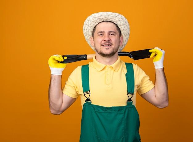Giovane giardiniere in tuta e cappello tenendo la pala sulla sua spalla guardando davanti sorridente fiducioso in piedi sopra la parete arancione