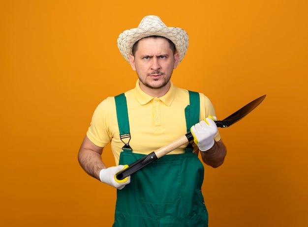 Giovane giardiniere in tuta e cappello tenendo la pala guardando la parte anteriore con la faccia seria in piedi sopra la parete arancione