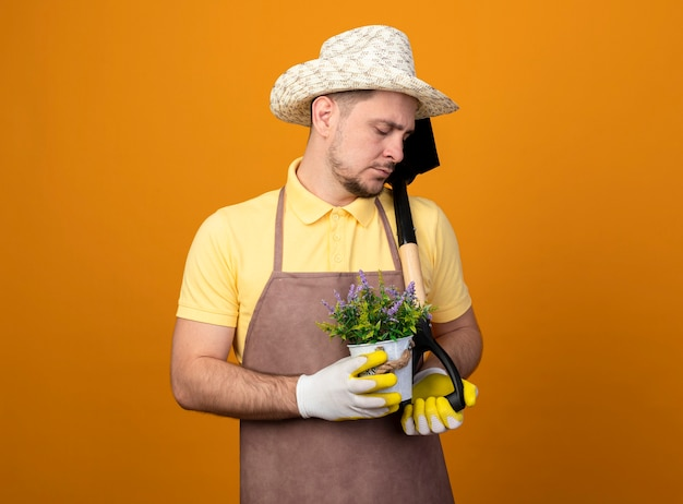 Giovane giardiniere in tuta e cappello che tiene pala e pianta in vaso guardando verso il basso con espressione triste in piedi sopra la parete arancione