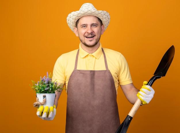 Giovane giardiniere in tuta e cappello tenendo la pala e la pianta in vaso guardando la parte anteriore sorridente con la faccia felice in piedi sopra la parete arancione