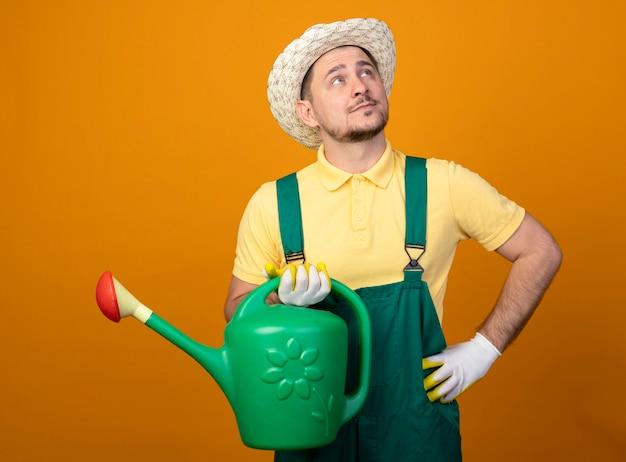 Giovane giardiniere in tuta e cappello tenendo annaffiatoio alzando lo sguardo perplesso sopra la parete arancione