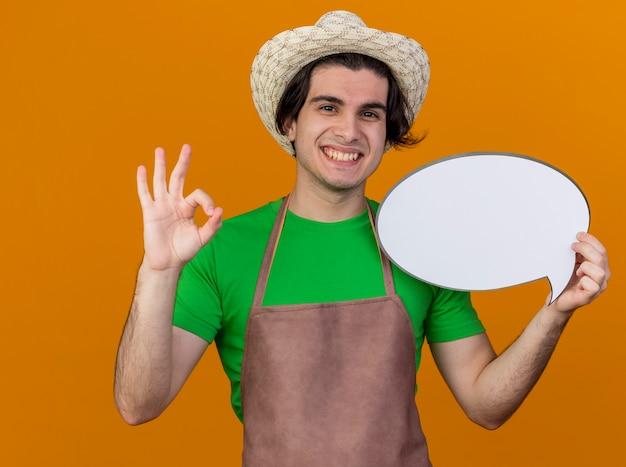 Giovane giardiniere uomo in grembiule e cappello tenendo vuoto discorso bolla segno guardando la telecamera sorridendo ampiamente mostrando segno ok in piedi su sfondo arancione