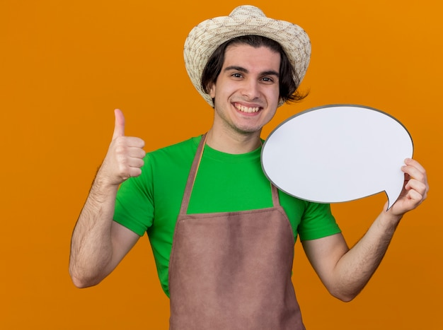 Young gardener man in apron and hat holding blank speech bubble sign looking at camera smiling cheerfully showing thumbs up standing over orange background