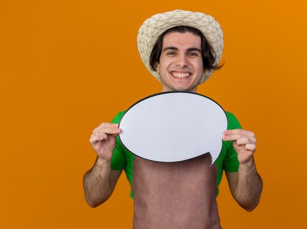Giovane giardiniere uomo in grembiule e cappello tenendo vuoto discorso bolla segno guardando sorridente con la faccia felice in piedi sopra la parete arancione