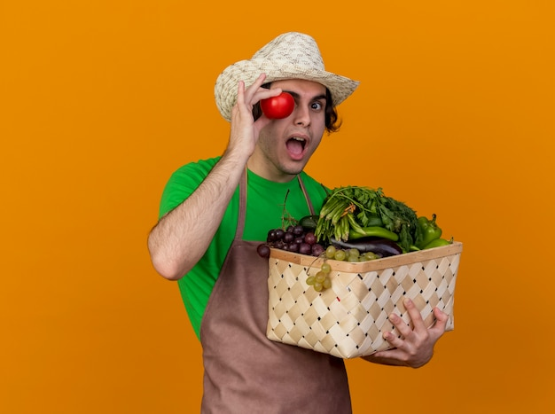 Young gardener man in apron and hat holding crate full of vegetables and fresh tomato near his eye smiling looking surprised standing over orange background