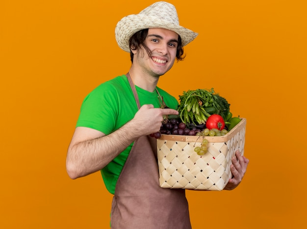 Giovane giardiniere uomo in grembiule e cappello azienda cassa piena di verdure guardando la telecamera sorridendo allegramente indicando con il dito indice alla cassa in piedi su sfondo arancione