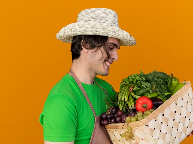 Giovane giardiniere uomo in grembiule e cappello tenendo la cassa piena di verdure guardandolo sorridente con la faccia felice in piedi sopra la parete arancione