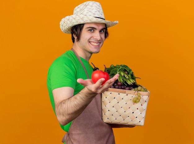 Giovane giardiniere uomo in grembiule e cappello tenendo la cassa piena di verdure mostrando pomodoro fresco sorridente con la faccia felice in piedi sopra la parete arancione