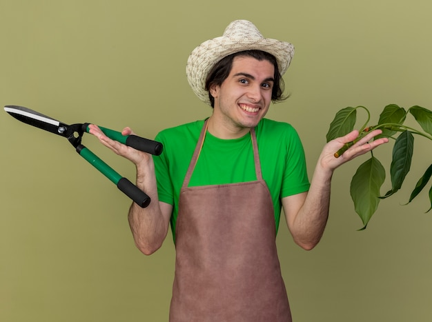 Young gardener man in apron and hat holding plant and hedge clippers looking at camera smiling with happy face standing over light background