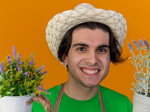 Giovane giardiniere uomo in grembiule e cappello in possesso di piante in vaso guardando sorridente ampiamente con faccia felice in piedi sopra la parete arancione