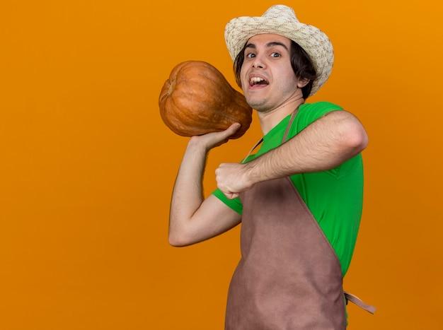 Giovane giardiniere uomo in grembiule e cappello tenendo la zucca andando a gettare int felice e allegro in piedi su sfondo arancione