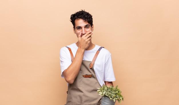 충격을 손으로 입을 덮고 젊은 정원사 남자