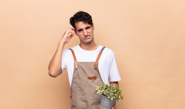 혼란스럽고 의아해하는 젊은 정원사 남자
