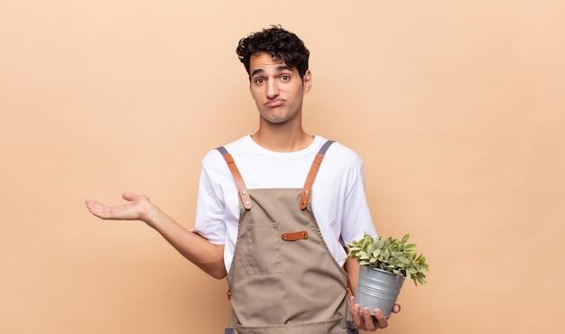 젊은 정원사 남자는 의아해하고 혼란스럽고 의심스럽고 가중하거나 재미있는 표현으로 다른 옵션을 선택하는 느낌