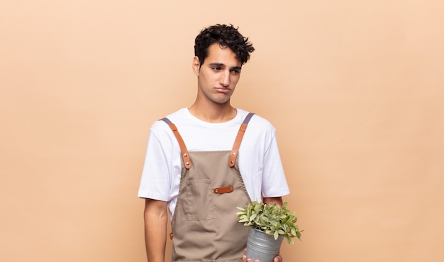 Young gardener man feeling sad, upset or angry and looking to the side with a negative attitude, frowning in disagreement