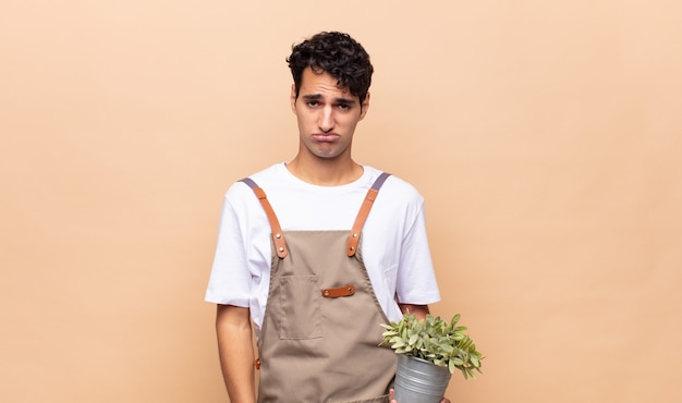 Young gardener man feeling sad and whiney with an unhappy look, crying with a negative and frustrated attitude