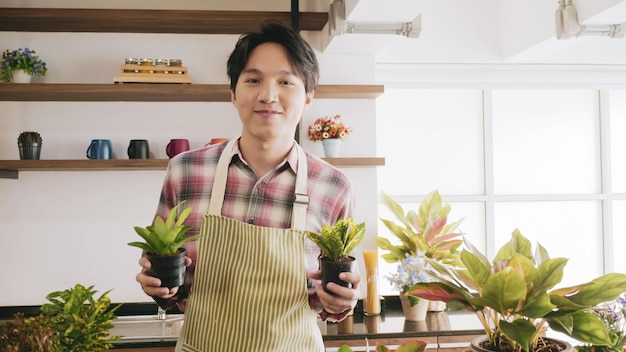 Young gardener man holding flowerpot in the room.