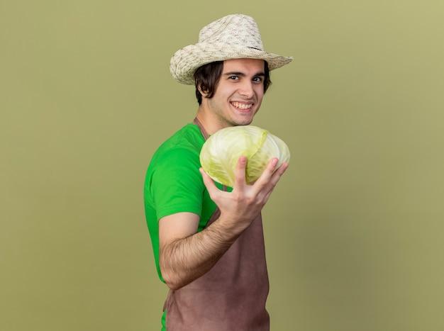 エプロンと帽子をかぶった若い庭師の男は、明るい壁の上に幸せで前向きに立っている顔に笑顔で見ているキャベツを保持しています