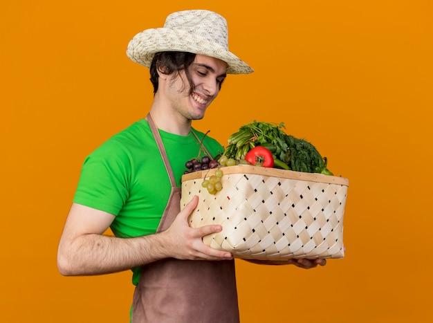 オレンジ色の壁の上に立っている幸せそうな顔で笑顔でそれを見ている野菜でいっぱいの木枠を保持しているエプロンと帽子の若い庭師の男