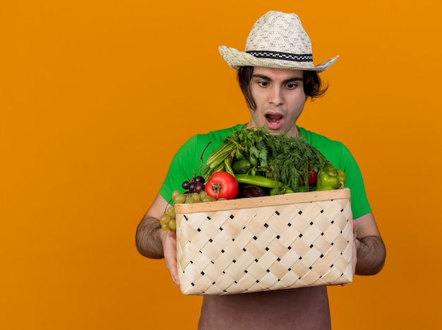 オレンジ色の背景の上に立って驚いて驚いたように見える野菜でいっぱいの木枠を保持しているエプロンと帽子の若い庭師の男
